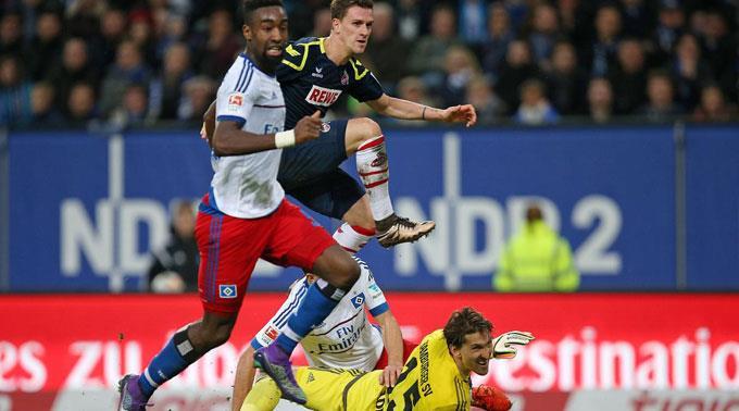 Kölns Simon Zoller erzielt das Tor zum 0:1 gegen Johan Djourou und Torhüter Rene Adler vom HSV.